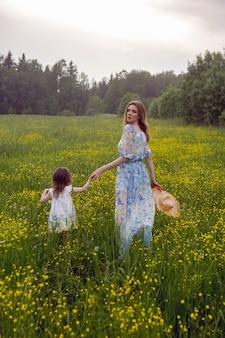 Moeder en dochter in jurken en een hoedentribune in een veld met gele bloemen in de zomerdag