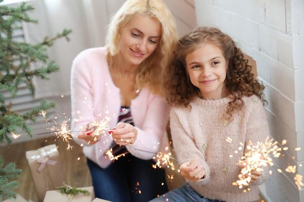 Moeder en dochter in kerst versierde woonkamer