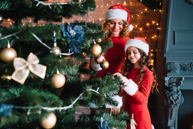 Moeder en dochter in kerstkostuums versieren de kerstboom met versieringen en speelgoed