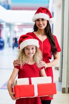Moeder en dochter in kerstmiskledij die zich met kerstmisgiften bevinden