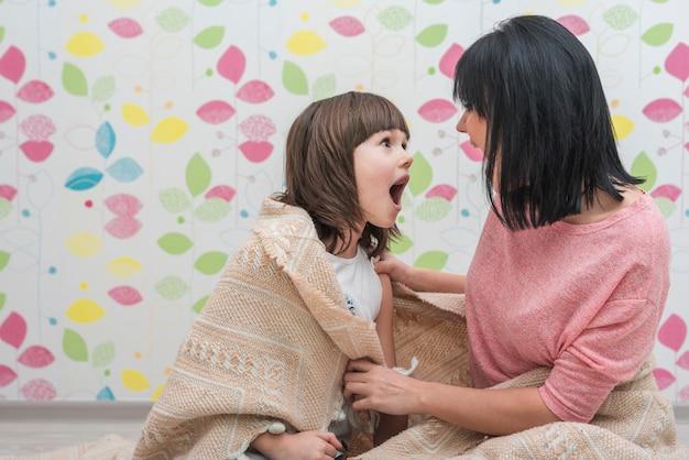 Moeder en dochter in lichte deken die gezichten maken