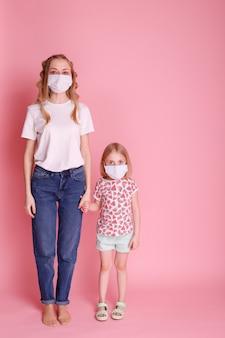 Moeder en dochter in medische maskers houden elkaars hand vast op roze oppervlak