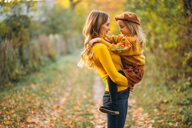 Moeder en dochter in parkhoogtepunt van bladeren
