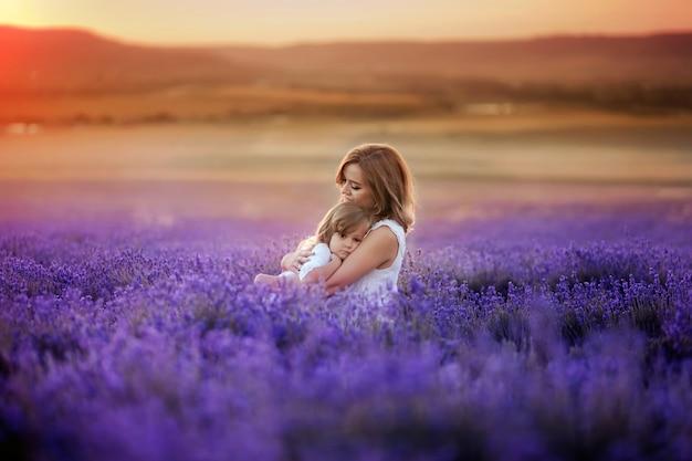 Moeder en dochter in prachtige witte jurken in een lavendelblauwe veld in de zomer bij zonsondergang.