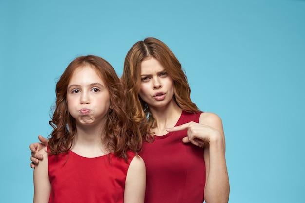 Moeder en dochter in rode jurken entertainment levensstijl leuke studio blauw.