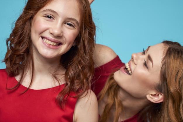 Moeder en dochter in rode jurken entertainment levensstijl leuke studio blauwe achtergrond