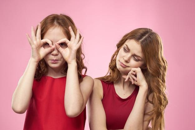 Moeder en dochter in rode jurken knuffels leuke grimas