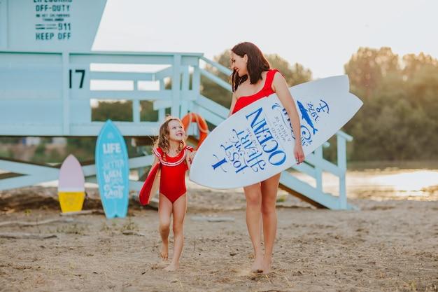 Moeder en dochter in rode zwemkleding met surfplank met citaat erop en badmeestertorenachtergrond