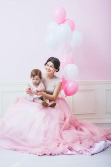 Moeder en dochter in roze interieur met vintage stoel en ballonnen in prachtige jurken Premium Foto