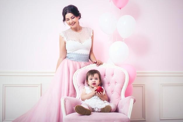 Moeder en dochter in roze interieur met vintage stoel en ballonnen in prachtige jurken