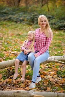 Moeder en dochter in roze shirts en spijkerbroek zitten op een boom in de herfst park.