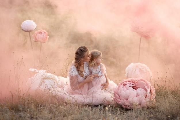 Moeder en dochter in roze sprookjesachtige jurken zitten in een veld omringd door grote roze decoratieve bloemen