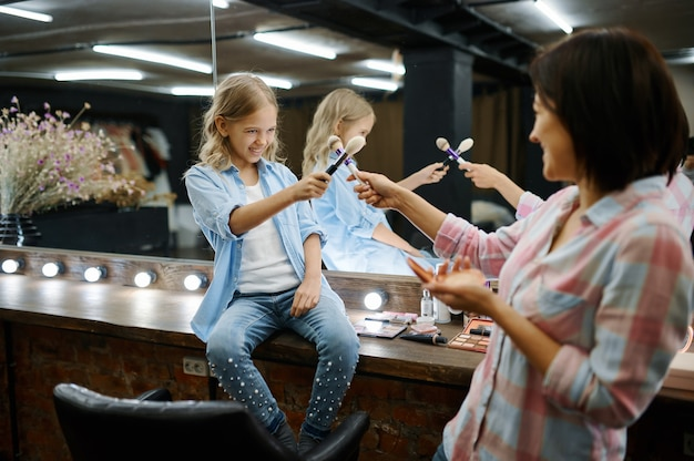Moeder en dochter in salon, make-upartiesten