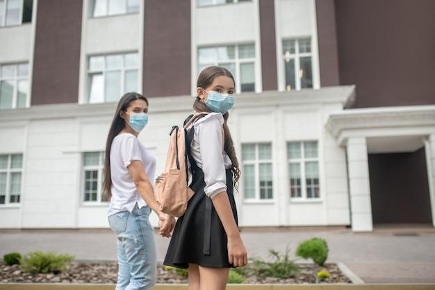 Moeder en dochter in schooluniform in beschermende maskers lopen hand in hand naar school