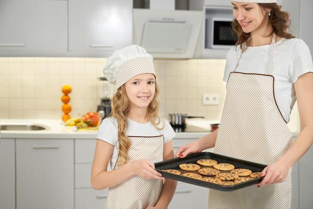 Moeder en dochter in schorten en chef-kok hoeden poseren met koekjes