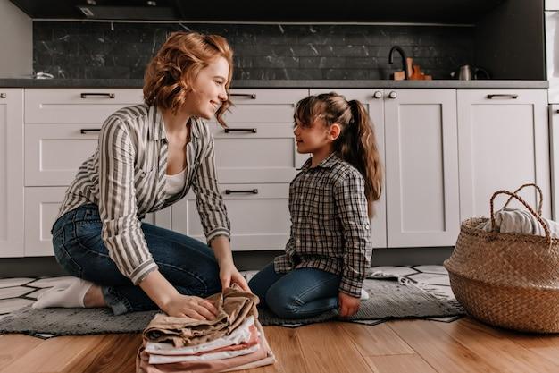 Moeder en dochter in soortgelijke outfit chatten lekker terwijl ze op de vloer van de keuken zitten en gewassen kleren opvouwen.
