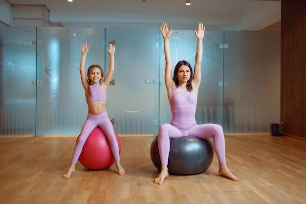 Moeder en dochter in sportschool, pilates met ballen, yogatraining.
