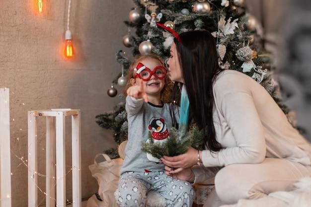 Moeder en dochter in trendy kledingpyjama's zitten bij de kerstboom met lichtjes en vieren de wintervakantie. kind meisje toont een vinger naar de camera