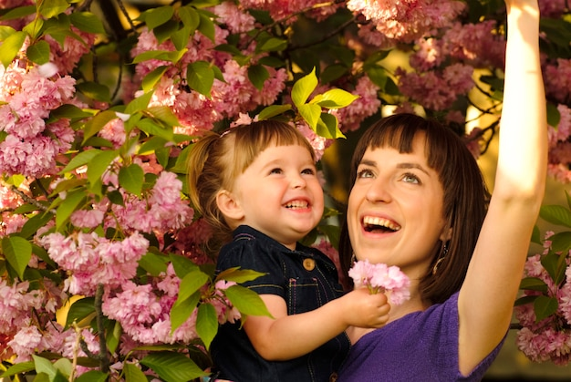 Moeder en dochter in tuin, onder de sakuraboom. de lente.