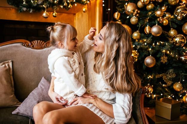 Moeder en dochter in witte en breiende kleren die, de winteravond samen thuis in een verfraaide woonkamer bij kerstavond koesteren glimlachen. familie gelukkigheid