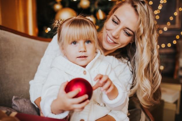 Moeder en dochter in witte en breiende kleren die, de winteravond samen thuis in een verfraaide woonkamer bij kerstavond koesteren glimlachen.