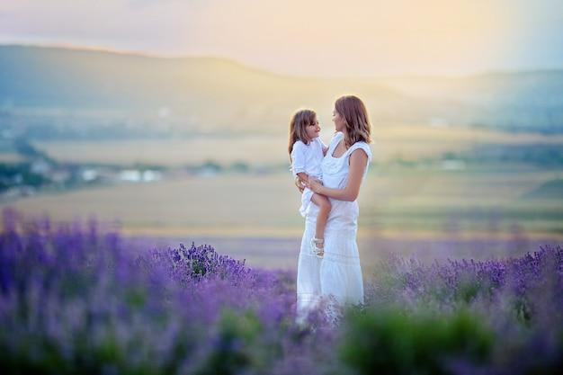Moeder en dochter in witte jurken op een wandeling bij zonsondergang op een lavendel veld