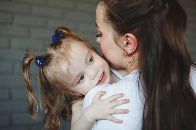Moeder en dochter in witte t-shirts en spijkerbroek, knuffelen en glimlachen in de studio op een donkergrijze bakstenen achtergrond. het concept van stijl casual.