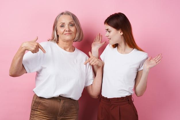 Moeder en dochter in witte t-shirts knuffelen samen familievriendschap