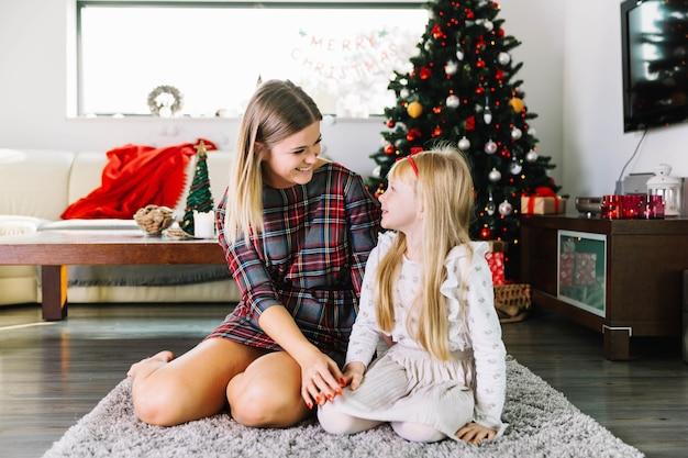 Moeder en dochter in woonkamer met kerstboom