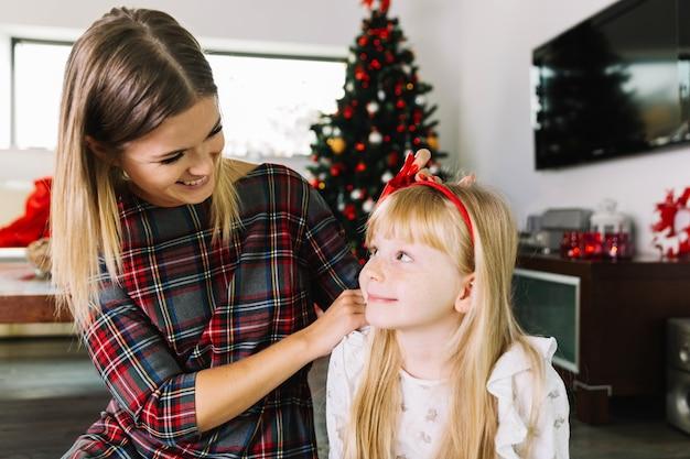 Moeder en dochter in woonkamer met kerstmisdecoratie