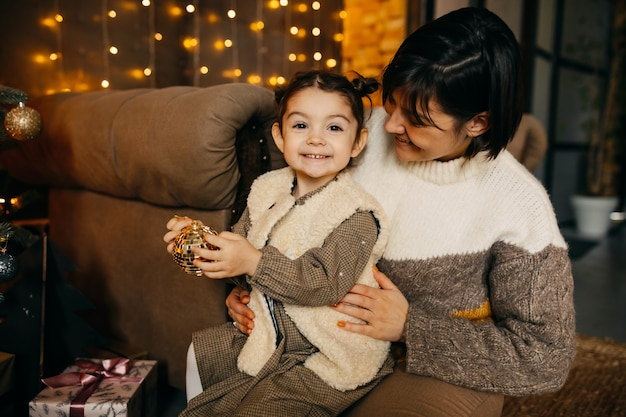 Moeder en dochter kerstboom thuis versieren