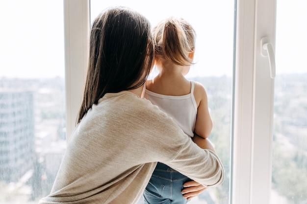 Moeder en dochter kijken door het raam