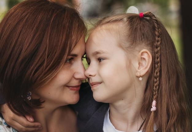 Moeder en dochter kijken elkaar aan. een close-up portret van een vrouw en een kind