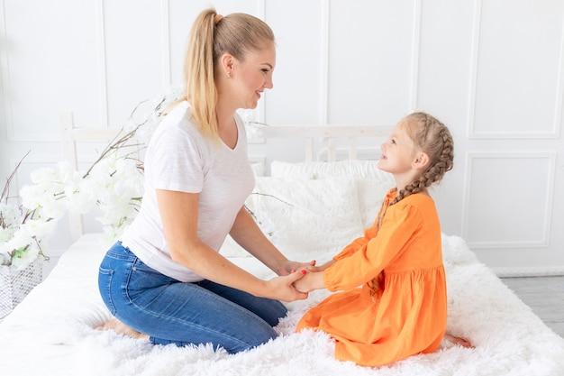 Moeder en dochter kijken elkaar aan op het bed thuis, het concept van liefde en moederschap of moederdag