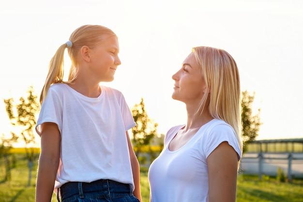 Moeder en dochter kijken elkaar aan op het platteland bij zonsondergang in de zomer Premium Foto