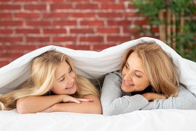 Moeder en dochter kijken elkaar onder blad