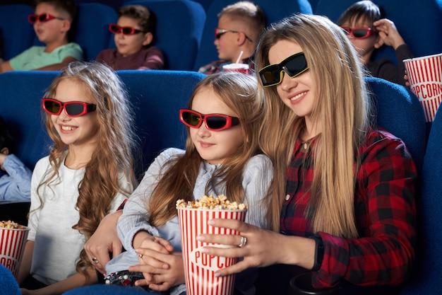 Moeder en dochter kijken naar 3d-film in de bioscoop.