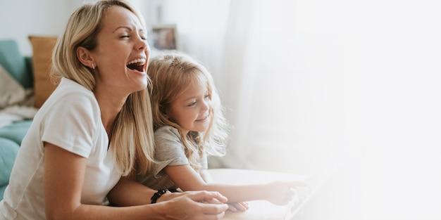 Moeder en dochter kijken naar een tekenfilm op een digitale tablet