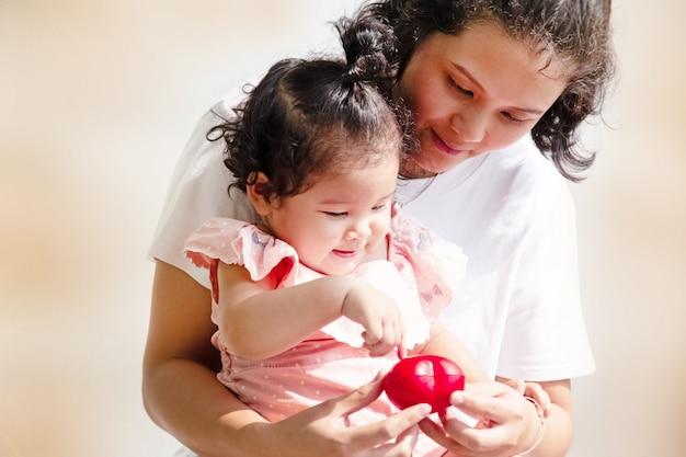 Moeder en dochter kijken naar kleine rode hart in handen
