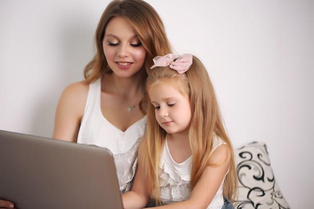 Moeder en dochter kijken naar laptop terwijl ze in bed liggen