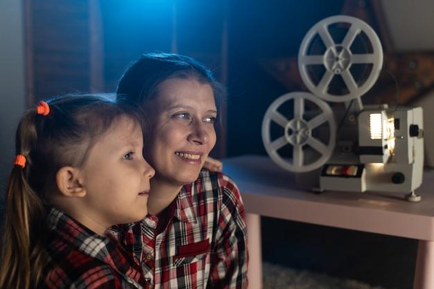 Moeder en dochter kijken naar oude film op retro vintage filmprojector thuis