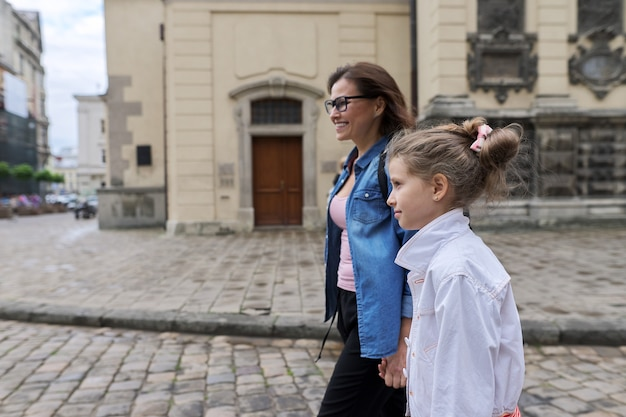 Moeder en dochter kind 8, 9 jaar oud lopen samen langs de straat van de oude stad, hand in hand