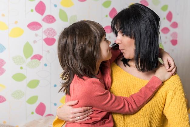 Moeder en dochter knuffelen en pruilende lippen