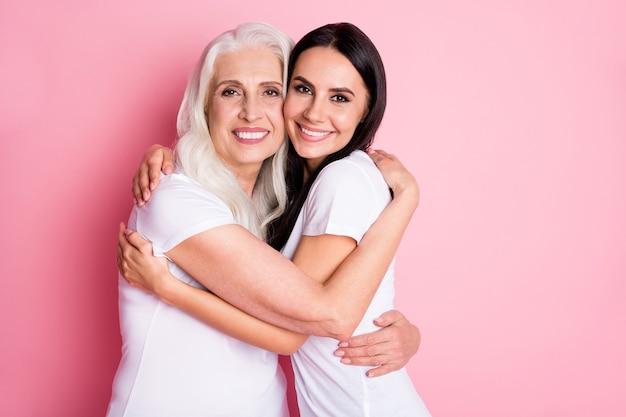 Moeder en dochter knuffelen geïsoleerd op roze