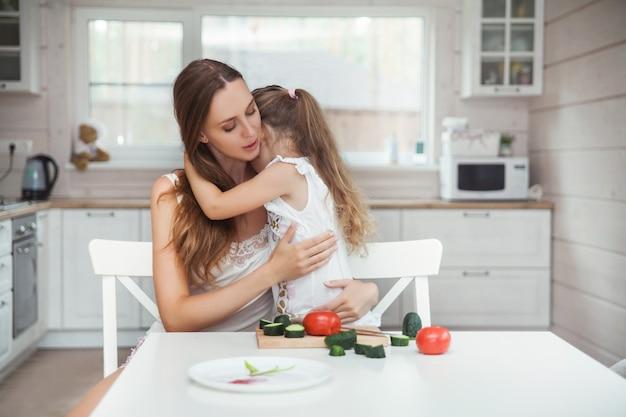 Moeder en dochter knuffelen in de keuken