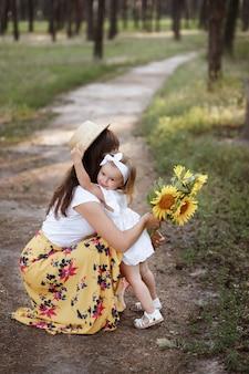 Moeder en dochter knuffelen in de zomer tijdens een wandeling