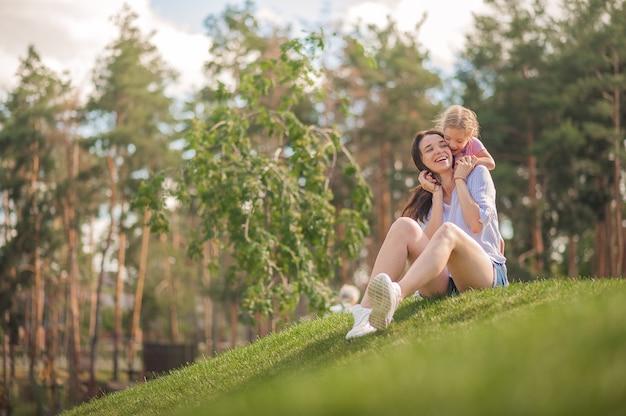 Moeder en dochter knuffelen in het park close-up