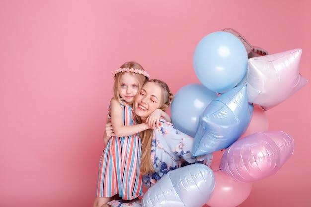 Moeder en dochter knuffelen met ballonnen op roze studiooppervlak