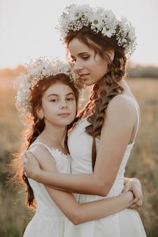 Moeder en dochter knuffelen samen in witte jurken met vlechten en bloemenkransen in bohostijl in de zomer