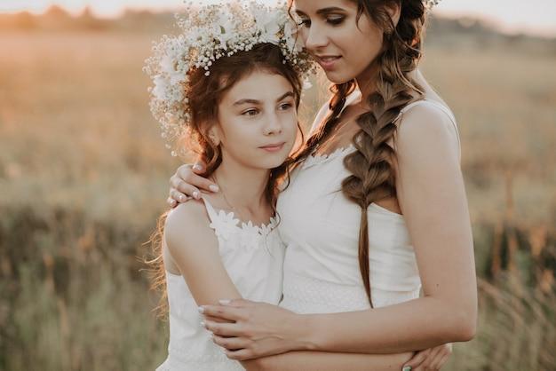 Moeder en dochter knuffelen samen in witte jurken met vlechten en bloemenkransen in de zomer